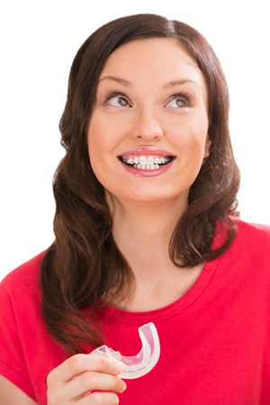 Closeup portrait of charming woman wearing orthodontic braces holding silicone trainer and smiling photo