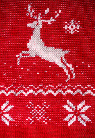 Real red knitted background with white Christmas deer and snowflakes photo
