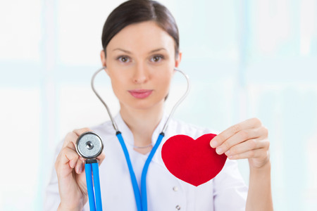 Female doctor with stethoscope holding red human heart at hospital photo