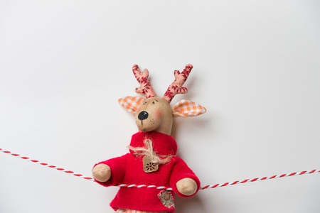 Handmade vintage Christmas deer hanging on a ribbon on white background with copyspace photo