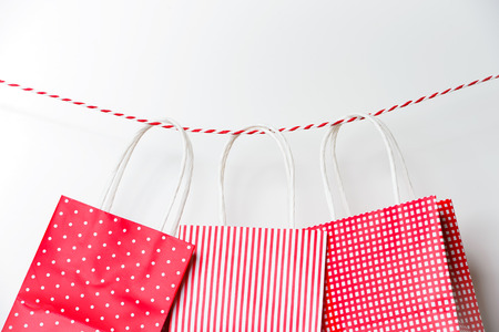 christmas shopping: Red gift package paper bags hanging on a ribbon Stock Photo