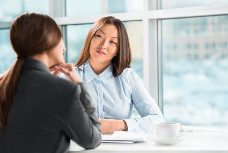 Two business women talking and signing contract at office Stock Photo