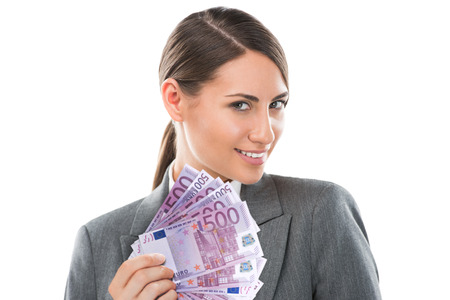 Business Woman holding and showing a lot of five hundred euro banknotes on a white isolated background Stock Photo