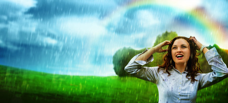 Young woman under storm rain. She is happy and wet photo