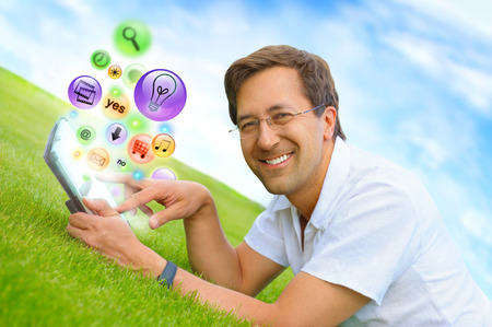 fingertip: Adult man using his tablet computer at countryside. Different icons appearing from touchscreen