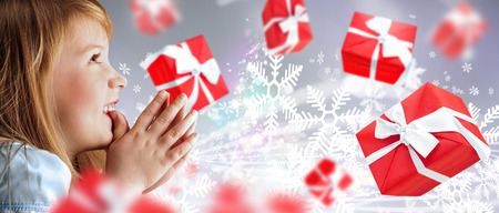 Portrait of young smiling praying girl looking up against silver fairy snowstorm background  Red gift boxes are flying around photo