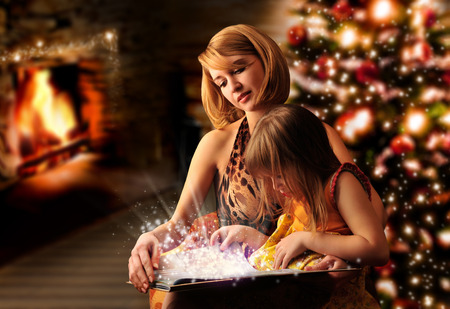 Young mother and her little daughter reading book sitting at the Christmas tree, fireplace photo