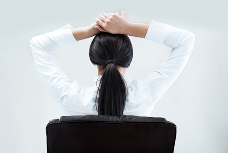 chear: Rear view of young business woman sitting at her office and thinking of her plans with hands behind head