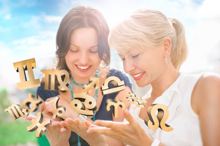 divining: Two women mother and daughter sitting at summer park and having fun while discussing horoscope and different zodiac symbols appearing from their hands. Lots of copyspace Stock Photo