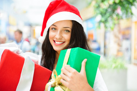 Portrait of young pretty woman wearing Santa Claus helper hat standing inside shopping mall smiling and holding christmas gifts photo