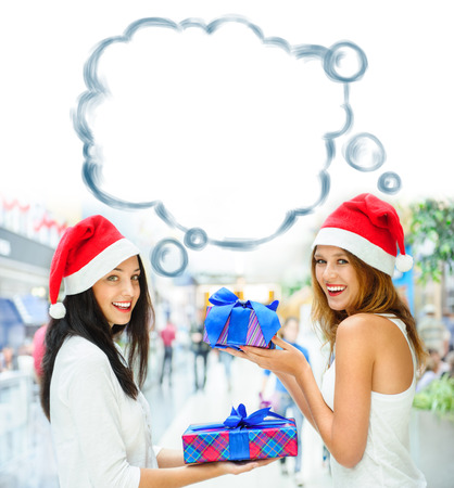 Young happy girls in Christmas hats. Standing together indoors and holding gift boxes. Blank cloud balloon overhead photo