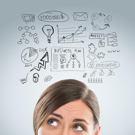 mujer pensando: Mujer de negocios joven que piensa de sus planes closeup retrato de la cara y de bocetos generales Foto de archivo