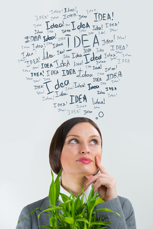 Idea concept. Young business woman with idea signs overhead photo