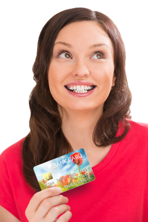 Young pretty woman holding plastic bank card and planning her spending photo