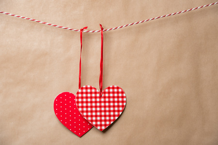 Two red textured hearts hanging on a ribbon. Old brown paper background photo