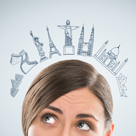 travel agent: Young pretty business woman dreaming about vacation and her trip to famous touristic destination. Architecture symbols overhead