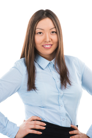 Portrait of a pretty young businesswoman standing on a white background with her hands on hips photo