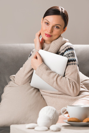 Smiling young woman using tablet computer at home at night before going to sleep. Cup of tea or coffee and cookies in front of her on table photo