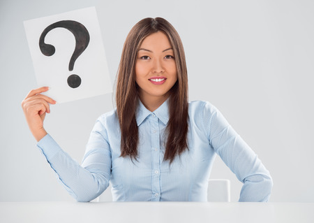 Portrait of business woman with question mark on placard over gray background photo