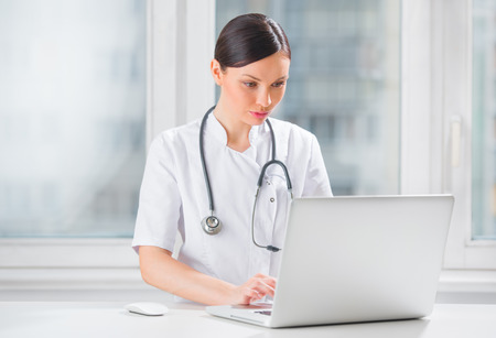Portrait of a female doctor using her laptop computer at clinic photo