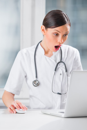 Portrait of a female doctor using her laptop computer at clinic and confused by something photo
