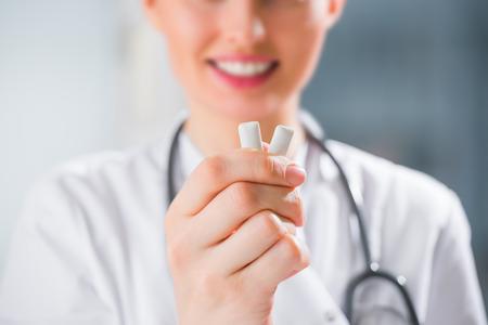 Female medical doctor - dentist - showing chewing gum. Dental care concept Zdjęcie Seryjne