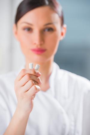 goma de mascar: Joven médico dentista femenina sosteniendo la goma de mascar y sonriente. Concepto de higiene oral