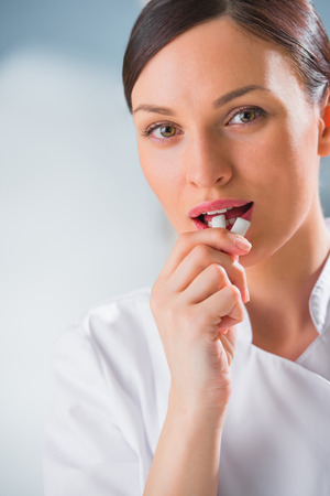 Young female dentist doctor holding chewing gum and smiling. Dental care concept photo