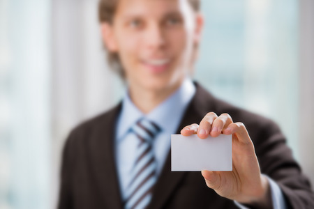 Business man handing a blank business card at his office photo