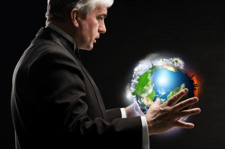 Senior business man holding planet in his arms and controlling it photo