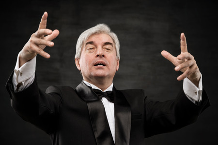 conducting: Closeup portrait of male orchestra conductor directing with his hands in concert. Business leading concept