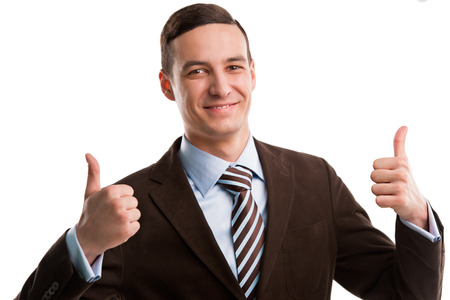 Portrait of a happy young business man showing thumbs up sign with two hands over white background photo