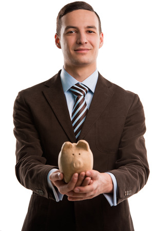 pennypinching: Young happy business man holding piggybank over white background