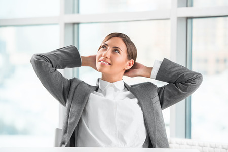 Portrait of smiling young business woman relaxing at office photo