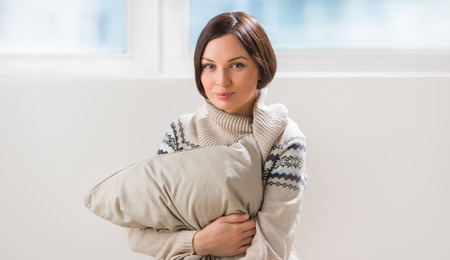 misses: An attractive young woman daydreaming and misses her couple, embracing pillow at living room