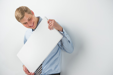 Portrait of an excited young businessman holding a blank board while leaning on wall at office photo