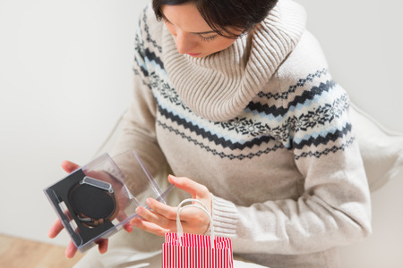 Portrait of a woman preparing to her husband or boyfriend surprise with a gift  - modern watch with timepiece on his birthday or valentines day or another holiday photo