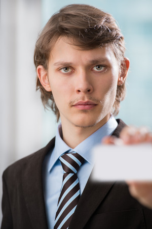 Business man handing a blank business card at his office Stock Photo - 27108621