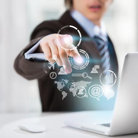 tecnologia informacion: Concepto de la tecnolog�a. Hombre de negocios y la interfaz virtual con iconos de la web y redes sociales Foto de archivo
