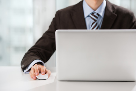 computer parts: Closeup of torso of confident business man wearing elegant suit working with his laptop at office Stock Photo