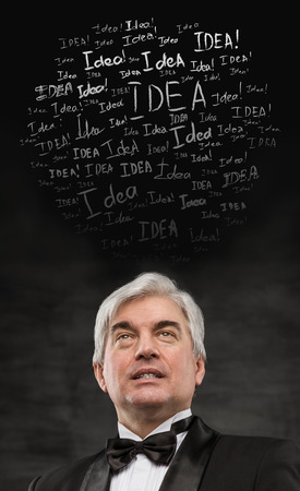Idea concept. Mature business man standing on black background with idea signs overhead photo