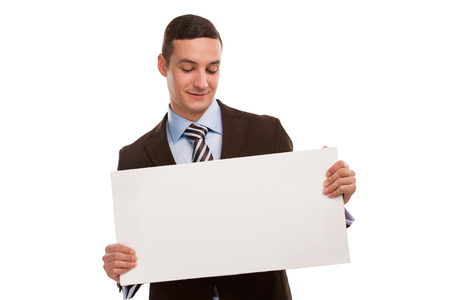 Portrait of a happy young business man holding a blank board for texting against white photo