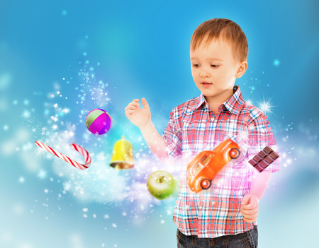 Little boy conjuring toys and confection with his hands photo