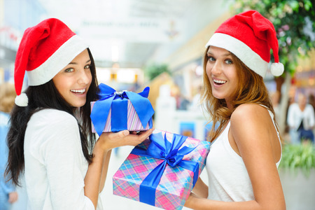 Young happy girls in Christmas hats. Standing together indoors and holding gift boxes photo