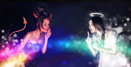 Portrait of angel and devil girls and copyspace between them. Stock Photo