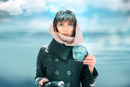 unawares: Young woman standing with cup of coffee or tea. Snow on her head and shoulders. Out of the blue concept Stock Photo