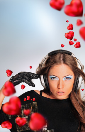 Young sexy woman in love and dancing. Red hearts flying around her. Hot passion music photo