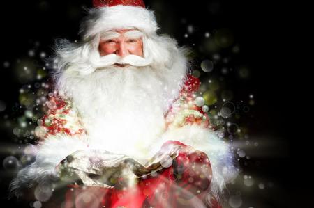 papa noel: Santa que se sienta en la sala de la Navidad y que mira en la bolsa Foto de archivo