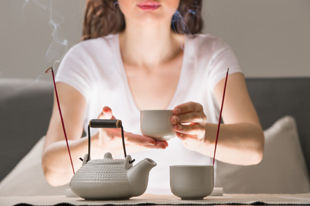 Young woman sitting in meditation pose in front of tea set and aroma sticks. Relaxation concept photo