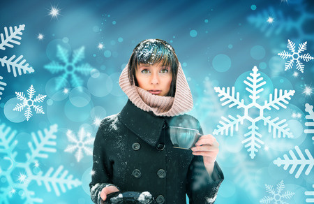 Young woman standing with cup of coffee or tea. Snow on her head and shoulders. Out of the blue concept photo